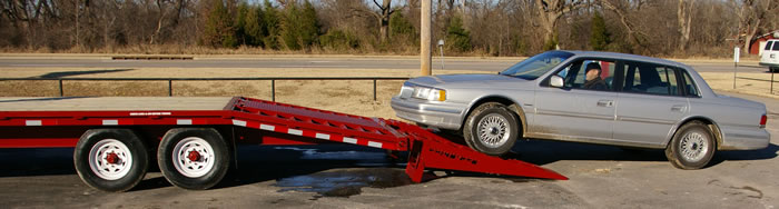 Twenty-six foot 7K trailer, equipped with six foot ramps being loaded with this low ground clearance vehicle.